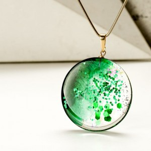 Naszyjnik zielony onym srebrnym łańcuszku.