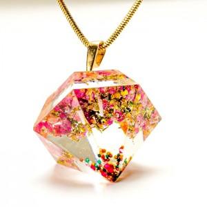 Długi naszyjnik z wisiorem w kształcie diamentu wypełnionego wrzoścem.
