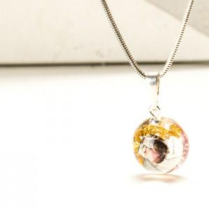 Naszyjnik z kwiatem wrzośca i płatkami złota w małej zawieszce.