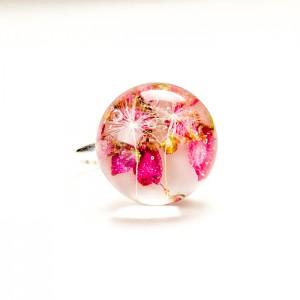 Srebrny pierścionek z różowym oczkiem wypełnionym wrzoścem i dmuchawcem.