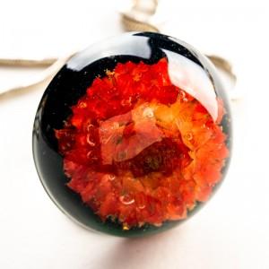 Biżuteria artystyczna z czerwonym kwiatem.