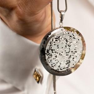 Srebrny naszyjnik z grafiką do białej koszuli.
