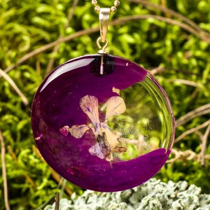 Fioletowy naszyjnik z kwiatem.