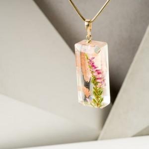 Naszyjnik pozłacany z gałązką różowych kwiatów wrzosu.