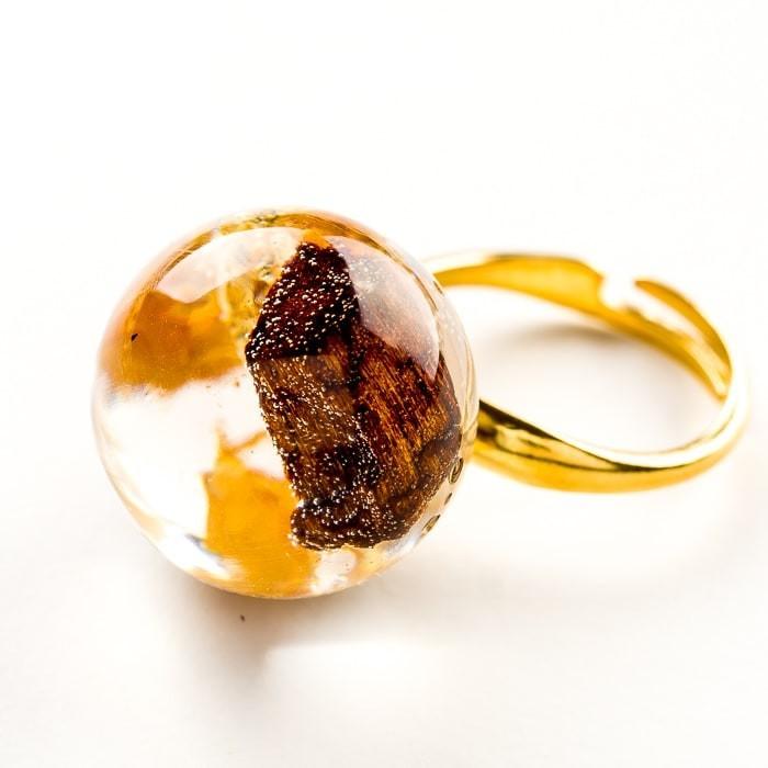 Pierścionek artystyczny pozłacany z brązowo złotym oczkiem z drewienkiem i płatkami złota
