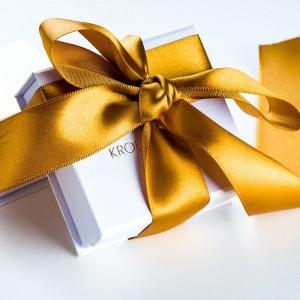 Srebrny naszyjnik z kwiatem i złotymi płatkami na srebrnym łańcuszku.